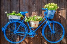 Kreative Wandgestaltung In Einem Garten Mit Einem Alten Fahrrad Und Farbenfrohen Blumen