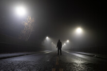 Low Angle, Looking Up At A Hooded Figure Standing In The Middle Of The Road On An Atmospheric Foggy Winters Night. UK.