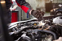 Mechanic Makes Diagnostics Of The Car In The Engine. Car Service And Audit By An Employee In A Large Car Service. Candle Replacement. Black Mittens And Car Tool