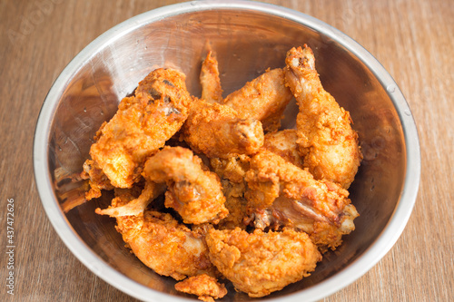 Fotografía Top view of crispy deep-fried chicken in a metal bowl put on a kitchen table
