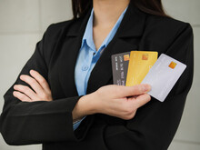 Close-up Of Three Mockup Credit Cards In A Businesswoman's Hands, A Businesswoman In A Black Suit With Arms Closed Is Holding Three Mockup Credit Cards In Her Right Hand.