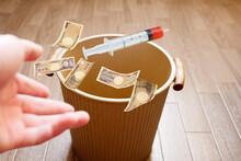 使用期限が切れて破棄されるワクチンのイメージでお金とともにゴミ箱へ投げ捨てる
