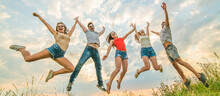 The Happy Friends Jumping On The Background Of The Clouds