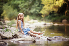 A Little Girl In The Forest On The River Sits On A Rock Splashing Water