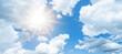 Leinwandbild Motiv Blue sky, cloudscae background banner panorama , with clouds and sun reflection / sunshine sunbeams