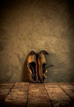 Old Rustic  Footwear Made Of Leather On Antique Tiles And Concrete Wall Background. Vintage Clothes Idea. Old National Shoes.