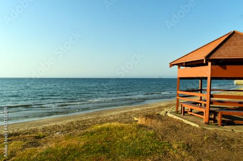 Fotografiet beach hut on the beach at sunset