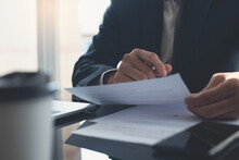 Signing Contract, Business Agreement And Deal Concept. Closeup Businessman Reading Before Signing Business Contract Documents