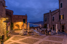 Borgio Verezzi, Italy. May 22th, 2021. Piazza Sant'Agostino At Night With People Sitting Outdoors At A Restaurant Table. In The Distance The View On The Ligurian Riviera In The Background.