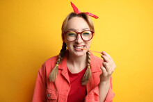 Fashionable Young Woman With Braids And Bright Makeup Chewing Bubblegum On Yellow Background