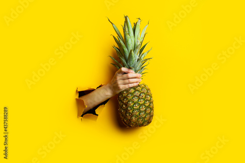 Woman hand holds a whole ripe pineapple in a torn yellow cardboard background Fototapeta