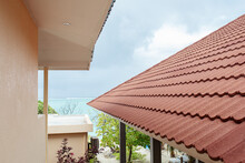 A Fragment Of A Building With A Modern Red Tile Roof. Architectural Details Of Housing Construction