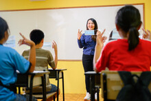 Asian Female Teacher And Student Wear A Mask To Prevent Coronavirus (COVID 19) Teaching Elementary School Students In A Rural School And Teach Them How To Wear Masks Correctly.