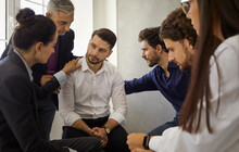 Group Of Different People Sitting In A Circle Supporting And Comforting A Sad Upset Young Man. Concept Of Psychological Help, Group Therapy And Overcoming Problems Together