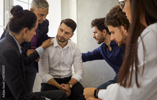 Obraz na płótnie Group of different people sitting in a circle supporting and comforting a sad upset young man