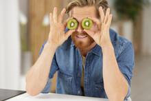 Man Holds A Kiwi At Eyes Level