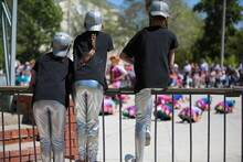 Three Middle School Girls In The Same Uniform Black T Shirt And Silver Baseball Cap And Leggings With Long Hair With A Pigtail Watch The Performance At A Children's Party Sitting On A Fence Outdoors