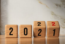 Cube Turns From 2021 To 2022 On Wooden Base And Marble Background