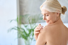 Back View Of Naked Gorgeous Middle Aged 50s Woman Applying Moisturizing Body Lotion After Shower. Advertising Of Bodycare Spa Procedures, Antiage Sun Protection Treatment Products Concept.