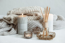 Cozy Home Composition With Candles, Aroma Sticks And A Knitted Element.