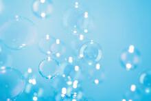 Beautiful Transparent Soap Bubbles Float On Blue Background.