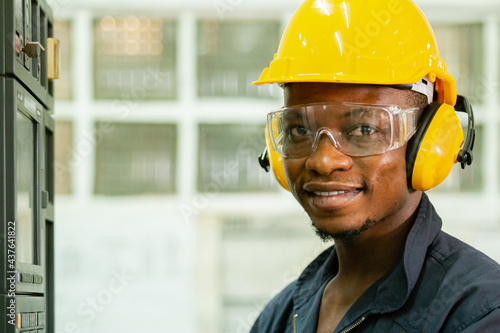 Fotografia, Obraz close up engineering male african american workers wear soundproof headphones and yellow helmet