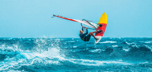Watersport: Windsurfer Jumping Among Waves Of The Blue Ocean During A Summer Vacation