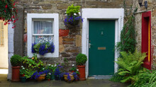 Picturesque Facade Of A Traditional Stone House With Ornate Colored Green Door And White Window. With Many Pots And Flowers In Front. Kirkwall, Scotland