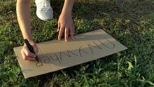 The Girl Writes Anywhere With A Marker On Cardboard. Hitchhiking. Trying To Stop The Car With A Sign