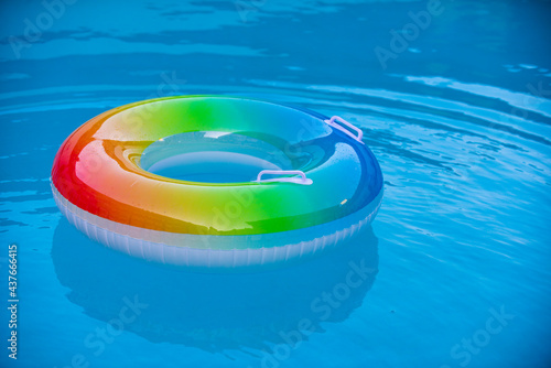 Pool float, ring floating in a refreshing blue swimming pool. Summer background.