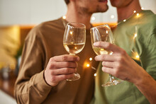 Same-sex Male Partners Kissing While Holding Wine Glasses