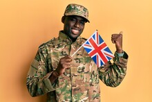 Young African American Man Wearing Army Uniform Holding United Kingdom Flag Pointing Thumb Up To The Side Smiling Happy With Open Mouth