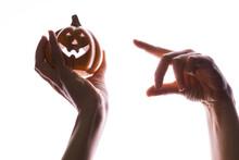 It's Halloween, Concept. Halloween Little Pumpkin With Face In Women's Hands, Pointing Finger At The Pumpkin,