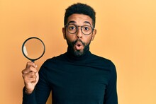 Handsome Hispanic Man With Beard Holding Magnifying Glass Scared And Amazed With Open Mouth For Surprise, Disbelief Face