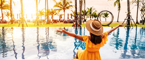 Stampa su Tela Young woman traveler relaxing and enjoying the sunset by a tropical resort pool