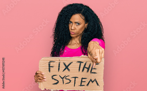 Canvastavla Middle age african american woman holding fix the system banner cardboard pointi