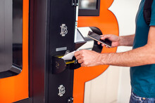 Bitcoin ATM. Man Using Bitcoin Atm To Buy Or To Sell Crypto Coins.
