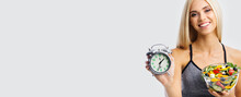 Woman In Sportswear With Alarm Clock And Greece Salad With Vegetables And Cheese, Isolated Over Grey Background With Copy Space. Girl In Dieting, Loss Weight And Time Interval Concept. Wide Image.