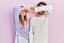 Young Hispanic Couple Wearing Casual Clothes Covering Eyes With Arm, Looking Serious And Sad. Sightless, Hiding And Rejection Concept
