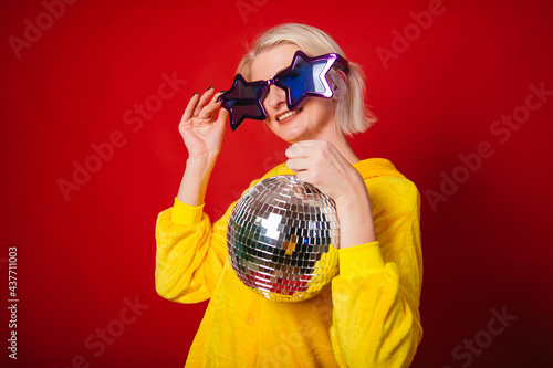 Fotografia A bright girl at a party in purple big glasses in the form of stars and in yellow camisole pajamas