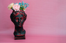 Planters In The Form Of A Painted Antique Head Of Venus In Black With Colored Carnations And Blue Gypsophila On A Pink Background. Banner With A Place For The Text
