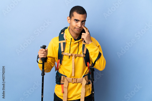 Fotografiet African American man with backpack and trekking poles over isolated background s