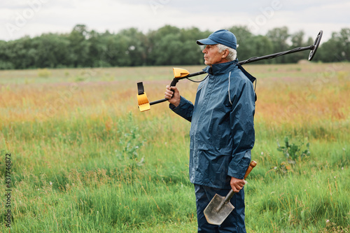 Fotografie, Obraz Gray haired senior treasure hunter posing with shovel and metal detector on his shoulder looking away, choosing place for searching coins or other artifacts
