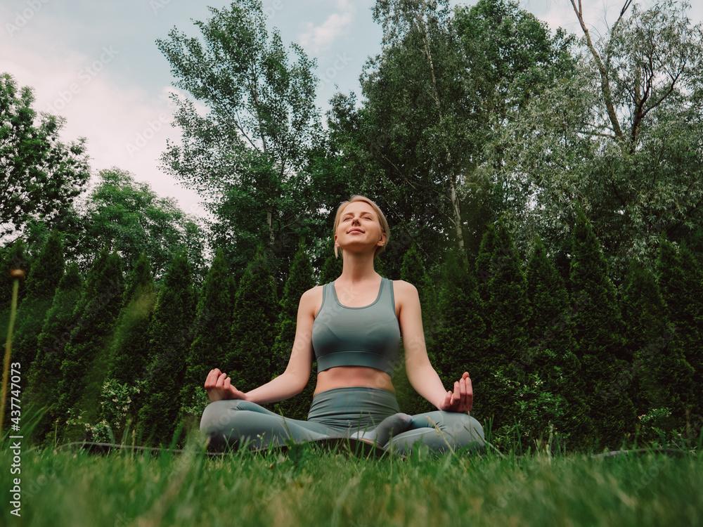 Leinwandbild Motiv - Masson : young woman practicing yoga on the grass in the garden