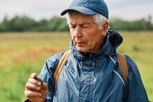 Closeup Portrait Of Treasure Hunter Man Wearing Cap And Jacket Holding Coin Found In Ground In Hands And Looking With Concentrated Facial Expression At His Finding.