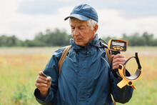 Senior Grey Haired Man Wearing Blue Jacket And Cap Posing Outdoor In Field Or Meadow And Holding Coin In Hands, Searching Artifacts With Metal Detector.