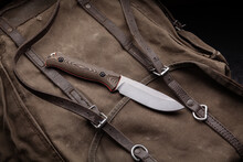 A Hunting Knife With A Wooden Handle On A Khaki Canvas Backpack. Weapons For Self-defense And Survival.