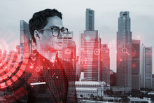 Eastern Prosperous Businessman In Suit Thinking About Career Opportunities At Research And Development Department At International Consultancy Company. Hologram Icons Over Singapore Background.