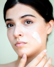 Close-up Of Caucasian Young Woman With Black Eyes Applying Skin Care Cream