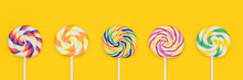 Five Fruit Rainbow Swirl Flat Lollipops In A Row Banner. Lollipop Candy Set. Different Sugar Candies On Sticks On Yellow Background.